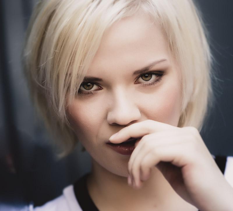 Portrait einer jungen blonden Frau die direkt in die Kamera blickt