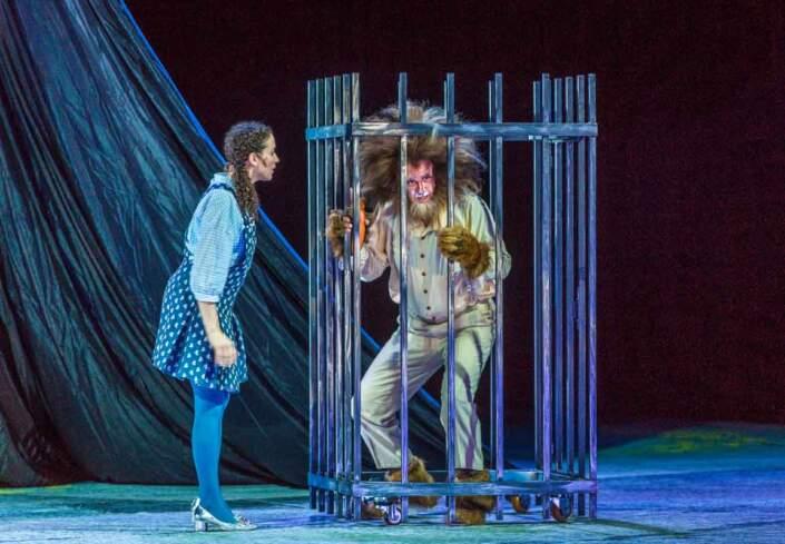 """Szene aus """"Der Zauberer von Oz"""" - Dorothy Gayle spricht mit dem Löwen der in einem Käfig gefangen ist"""